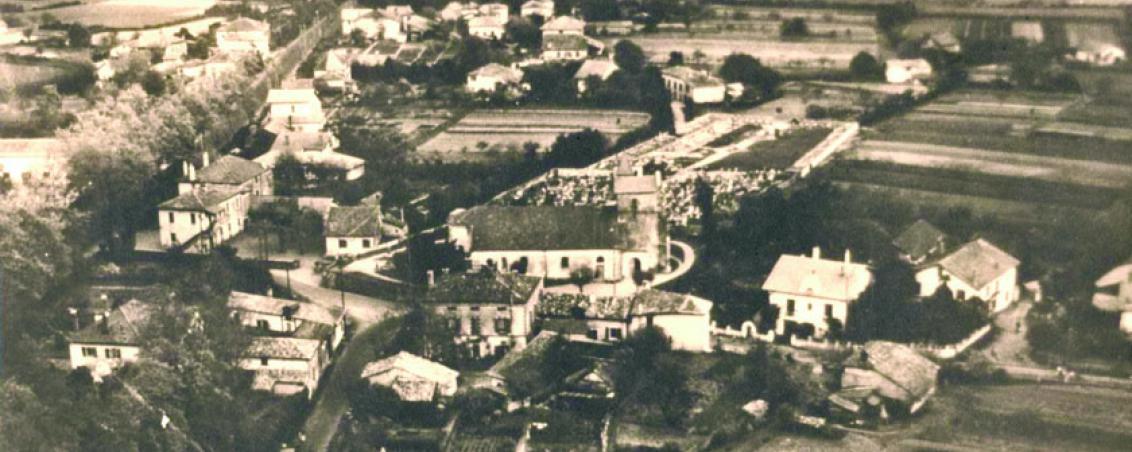 Église Saint Vincent et actuelle place Dous Haous au début des années 1950. Dans la partie supérieure gauche, la RD810 (ex RN10) bordée de platanes