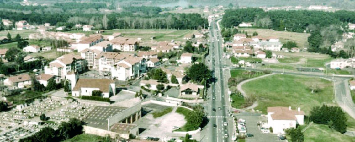 Vue aérienne de 1998, direction Bayonne Ondres. A droite de la RD810, l'ancienne mairie, à gauche, la salle Jacques Duclos, le cimetière, l'église Saint Vincent et la place Dous Haous